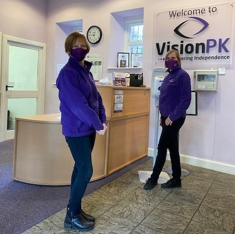 Two female VisionPK employees standing at VisionPK reception, looking at camera, wearing masks